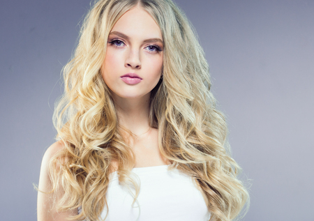 Beautiful blonde girl with long curly hair over purple background. Studio shot. 스톡 콘텐츠 - 115535712