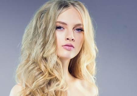 Beautiful blonde girl with long curly hair over purple background. Studio shot. 스톡 콘텐츠 - 115535821