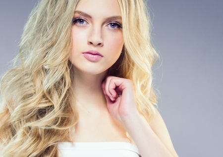 Beautiful blonde girl with long curly hair over purple background. Studio shot. 스톡 콘텐츠 - 115535820