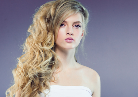 Beautiful blonde girl with long curly hair over purple background. Studio shot. 스톡 콘텐츠 - 115532368