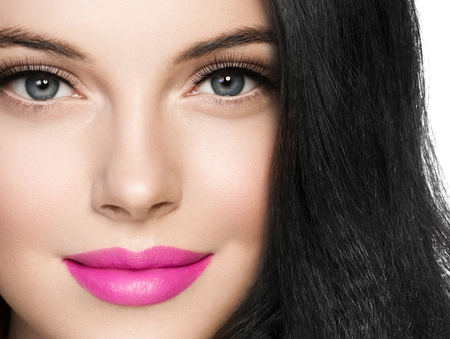 Beautiful brunette woman with pink lipstick and long black hair isolated on white. Studio shot.