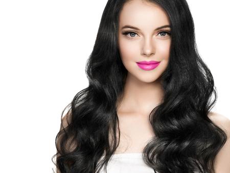 Hermosa mujer morena con extensión de pestañas y lápiz labial rosa peinado rizado largo morena. Foto de estudio. Foto de archivo
