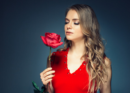 Woman with rose flower. Beauty female portrait with beautiful rose flower and salon hairstyle over gay blue background blonde hair and red dress. Studio shot.