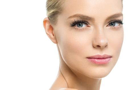 Hermosa mujer con rostro de belleza de cabello rubio de maquillaje natural de piel sana con pestañas de belleza y labios rosados. Foto de estudio. Foto de archivo