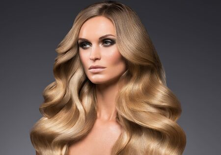 Femme blonde cheveux longs bouclés maquillage de mode naturel. Prise de vue en studio. Banque d'images