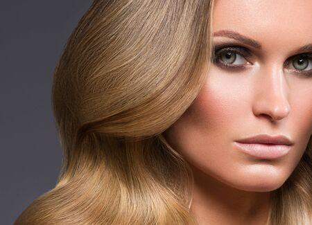 Blond woman long hair curly natural fashion makeup. Studio shot. Archivio Fotografico