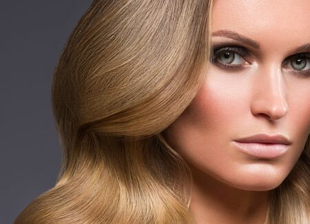 Blond woman long hair curly natural fashion makeup. Studio shot. Reklamní fotografie
