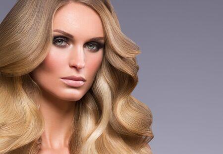 Blond woman long hair curly natural fashion makeup. Studio shot.