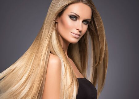Hair beautiful long blond hairstyle woman fashion makeup healthy skin and hair black background. Studio shot.