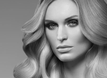 Healthy curly hair woman long blonde hairstyle female. Studio shot. Monochrome. Gray. Black and white.