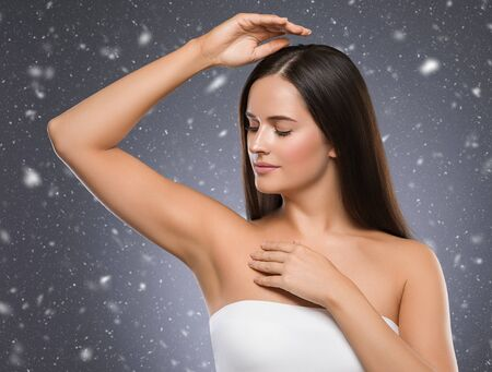 Winter armpit woman winter concept snowflakes background woman hand up beauty depilation. Studio shot. Banque d'images