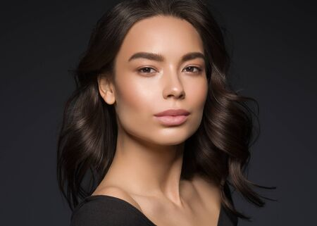 Asian beauty female black background curly black hair natural make up. Studio shot.