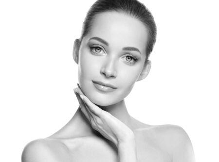 Frauenschönheitsgesicht gesundes Haut natürliches Make-up schönes junges Modell. Studioaufnahme. Einfarbig. Grau. Schwarz und weiß.