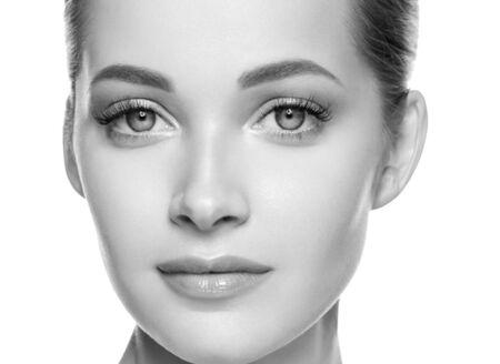 Beauté femme visage peau saine maquillage naturel beau jeune modèle. Prise de vue en studio. Monochromes. Gris. Noir et blanc.