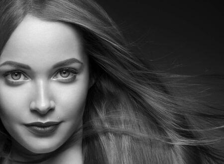 Beautiful hair woman long smooth brunette hairstyle beauty healthy hair female model portrait.  Studio shot. Monochrome. Gray. Black and white. Фото со стока