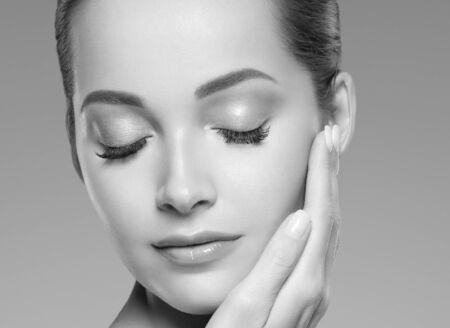 Hautpflegefrauenschönheitsgesicht gesundes Gesichtshautkosmetikmodell emotionales andhappy. Studioaufnahme. Einfarbig. Grau. Schwarz und weiß.