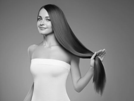 Beautiful hair woman long smooth hairstyle beauty concept. Studio shot. Monochrome. Gray. Black and white.