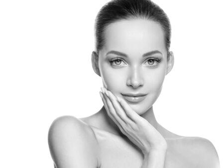 Woman beauty face healthy skin natural makeup beautiful young model. Studio shot. Monochrome. Gray. Black and white. Фото со стока