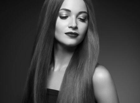 Beautiful hair woman long smooth brunette hairstyle beauty healthy hair female model portrait. Studio shot. Monochrome. Gray. Black and white. Reklamní fotografie