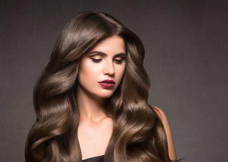 Hairte hairstyle model beauty woman long curly brunat. Studio shot.