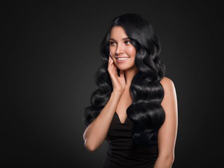 Black hair woman long curly beauty cosmetic concept over black background. Studio shot.