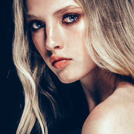 Beautiful Blonde Woman Beauty Model Girl with perfect makeup and hairstyle over black background.