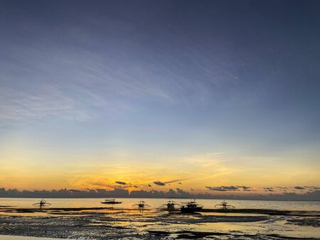 Incredibly beautiful, magical sunset, sunrise in the tropics with shades of orange, yellow.Calm sea with dark silhouettes of boats on the horizon background sky and clouds.Low tide on a sandy beach