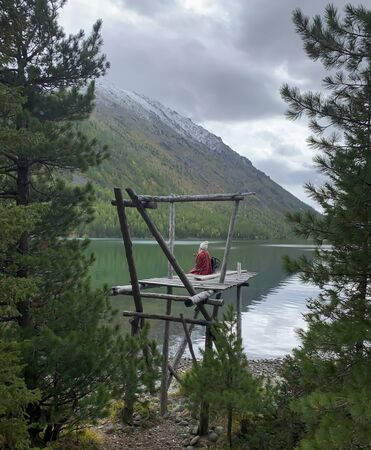 Blonde girl from the back sits in plaid.Beautiful lake, forest,snow mountains