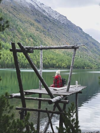 Blonde girl from the back sits in plaid.Beautiful green lake,forest,mountains Reklamní fotografie