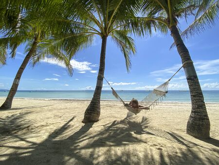 Girl resting and swinging on hammock in paradise resort.Beautiful sandy white beach with a turquoise sea in grove with palm trees. Shadows on sand.