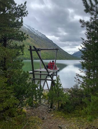 Loving couple girl,guy sit with their backs in plaid,look at lake,mountains Stock fotó