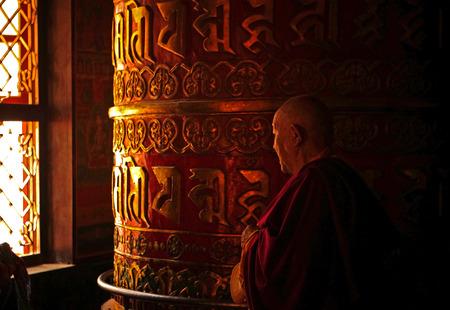 cassock: Monk Rotating a Prayer Wheel Stock Photo