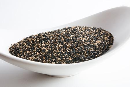 white sesame seeds: Mix of black and white sesame seeds in white bowl