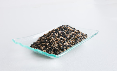 white sesame seeds: Mix of black and white sesame seeds on a glass plate