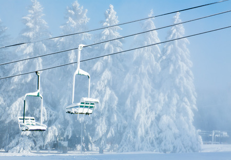 Two snow-covered chairs of not working chair-lift photo