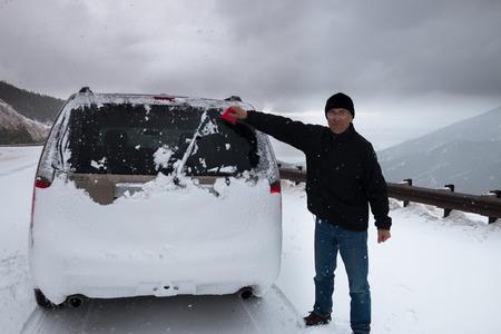 retrovisor: Tormenta de nieve en las monta�as - hombre limpia de nieve de retrovisor ventana de su coche Foto de archivo