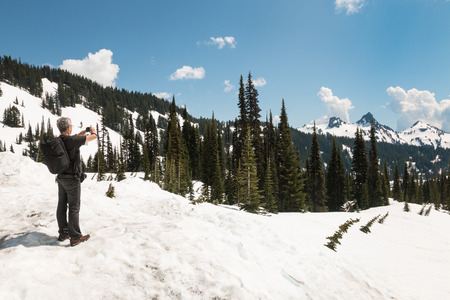 Man in summer clothes stand on snow and takes pictures of mountain peaks photo