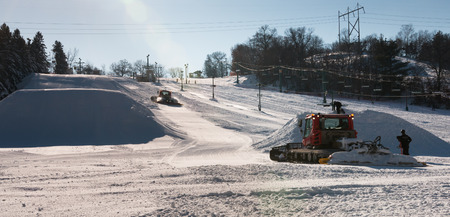 snow grooming machine: Workers build terrain park at  ski field, Afton Alps, Minnesota, USA Stock Photo