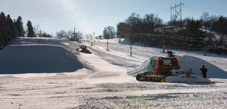 snow grooming machine: Workers build terrain park at  ski field, Afton Alps, Minnesota, USA Stock Photo