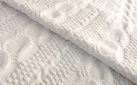 coverlet: White knitted blanket folded diagonally