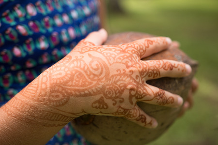 on temporary: Girls hand with temporary henna tattoo holds a coconut Stock Photo