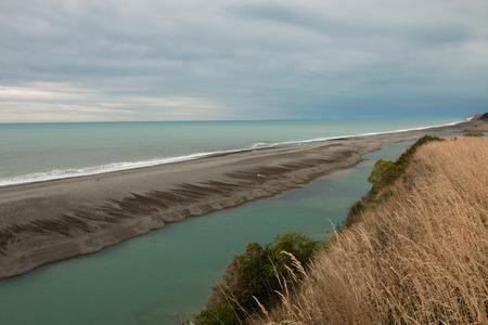 alongside: Hurunui RIver flows along ocean shore Canterbury New Zealand
