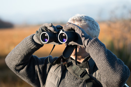 gray haired: Gray haired man with binocular Stock Photo