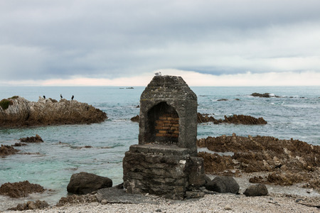 mudstone: Brick old-fashioned fireplace on ocean shore, Kaikoura, New Zealand Stock Photo