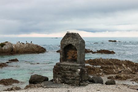 kaikoura: Brick old-fashioned fireplace on ocean shore, Kaikoura, New Zealand Stock Photo