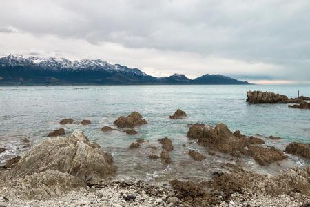 kaikoura: Snow covered mountains on ocean shore, Kaikoura, New Zealand Stock Photo