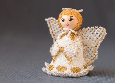 beaded: Toy beaded angel on gray background