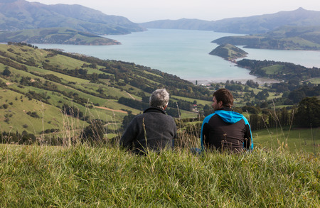 frienship: Two men sit in the grass on the top of hill and look at harbour, view from behind