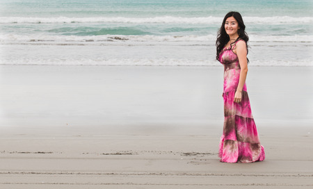 stays: Smiling young woman in long dress stays on the ocean shore