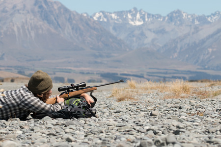 riffle: Hunter with riffle on background of mountains